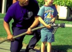 Hayward fireman teaching a child about firefighting.
