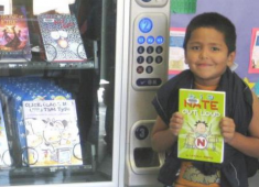 Child checking out a book at a Hayward Library book vending machine.